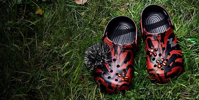 Two Crocs shoes in red and black on a turf surface.