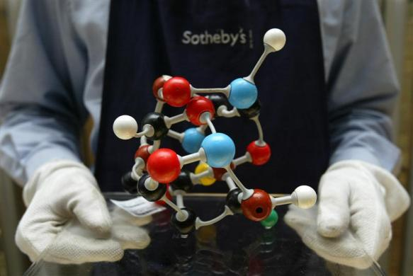 An auctioneer's assistant holds up the artwork 'Molecular Structure' by British artist Damien Hirst at Sotheby's in London, October 14, 2004.