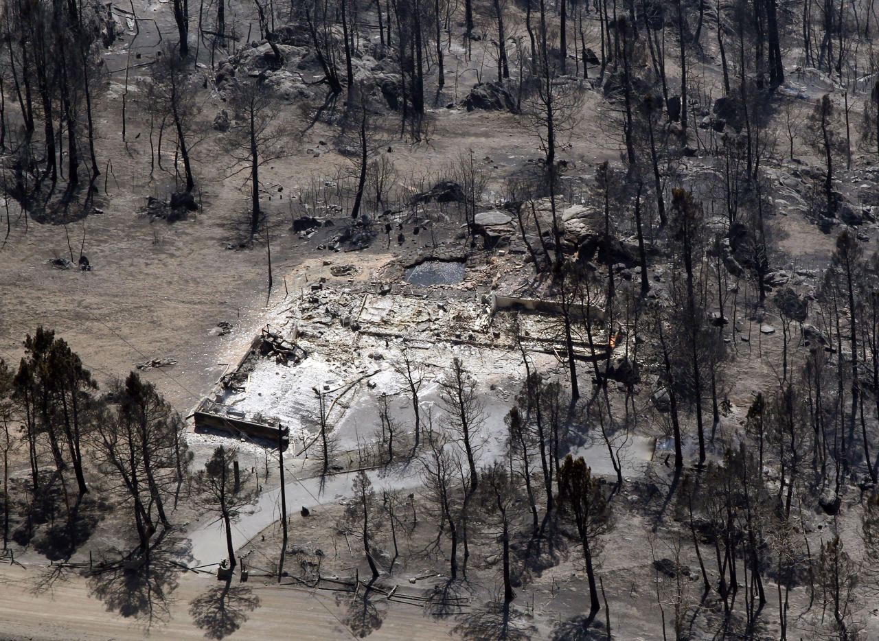 This aerial view shows the remains of a structure burned to its foundation after the Lower North Fork Wildfire rolled trhough the foothills community of Conifer, Colo., southwest of Denver on Tuesday, March 27, 2012. Firefighters are now able to actively battle the blaze on the ground that started on Monday and has already destroyed at least 16 homes in the rugged terrain. (AP Photo/David Zalubowski)