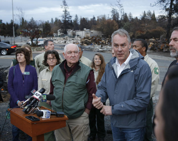 Interior Secretary Ryan Zinke, right, answers a reporter's question after touring fire-ravaged Paradise, Calif., with Agriculture Secretary Sonny Perdue, center, on Monday. (Photo: Rich Pedroncelli/AP)