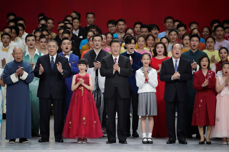 Chinese President Xi Jinping, outgoing Macau Chief Executive Fernando Chui and incoming chief Ho Iat-seng sing with performers onstage during a cultural performance in Macau