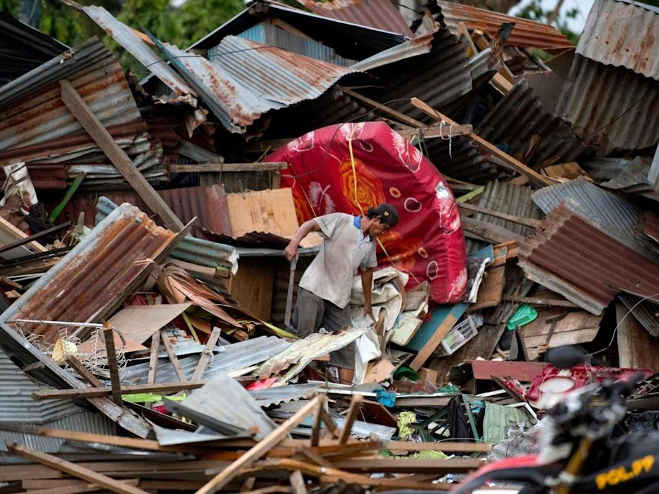 A man looks for his belongings amid the debris of his destroyed house in Palu (AFP/Getty )