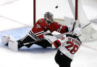 Chicago Blackhawks goalie Cam Ward, left, cannot stop a goal by New Jersey Devils defenseman Damon Severson, right, during the first period of an NHL hockey game Thursday, Feb. 14, 2019, in Chicago. (AP Photo/Nam Y. Huh)