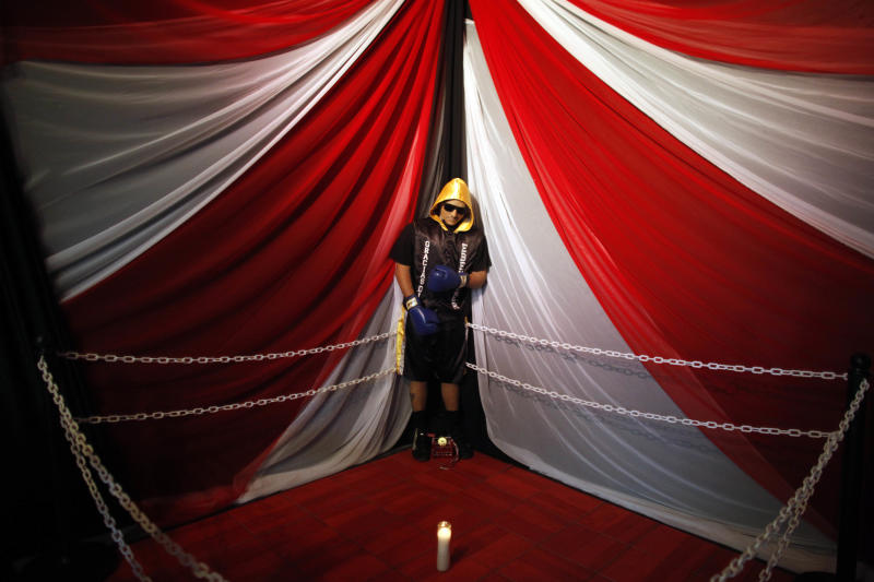 The body of boxer Christopher Rivera, who was shot to death on Sunday, is propped up in a fake boxing ring during his wake at the community recreation center within the public housing project where he lived in San Juan, Puerto Rico, Friday, Jan. 31, 2014. Elsie Rodriguez, vice president of the Marin funeral home, explained that Rivera had asked his family that if he died, he wanted his funeral to make reference to his boxing career. (AP Photo/Ricardo Arduengo)