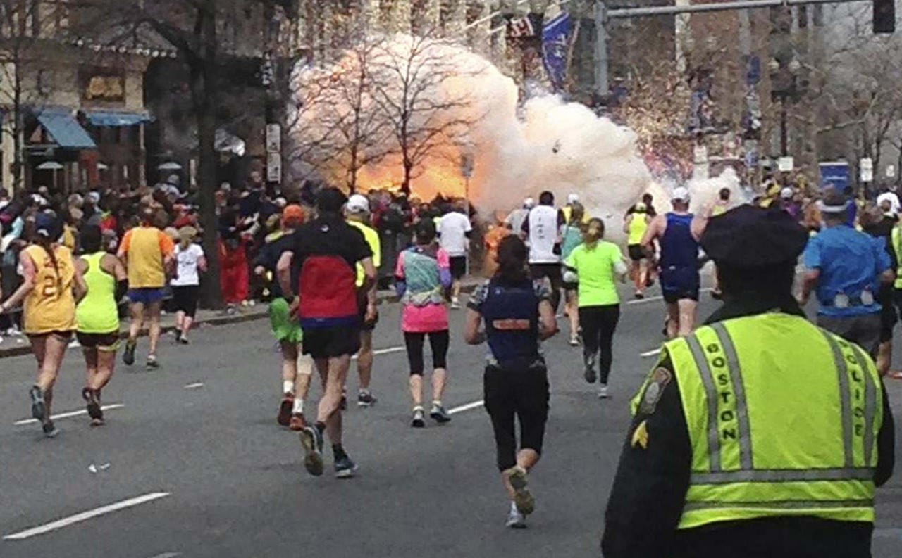 <p>Runners continue to run toward the finish line of the Boston Marathon as an explosion erupts on April 15, 2013. Two explosions shattered the euphoria at the finish line, sending authorities out to carry off the injured while the stragglers were rerouted away from the smoking site of the blasts. (Photo: Dan Lampariello/Retuters) </p>