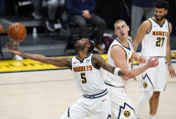 Denver Nuggets forward Will Barton, left, reaches out to pull in a rebound as center Nikola Jokic and guard Jamal Murray, right, look on in the second half of an NBA basketball game against the Oklahoma City Thunder Tuesday, Jan. 19, 2021, in Denver. (AP Photo/David Zalubowski)