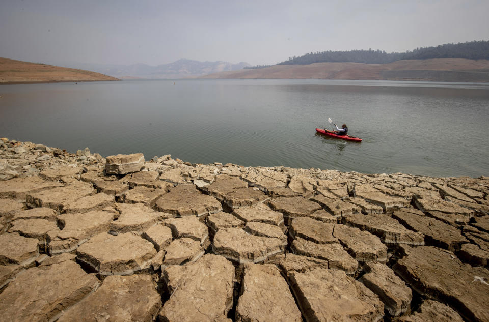 A kayaker paddles in Lake Oroville as water levels remain low due to continuing drought conditions in Oroville, Calif., Sunday, Aug. 22, 2021. (AP Photo/Ethan Swope)