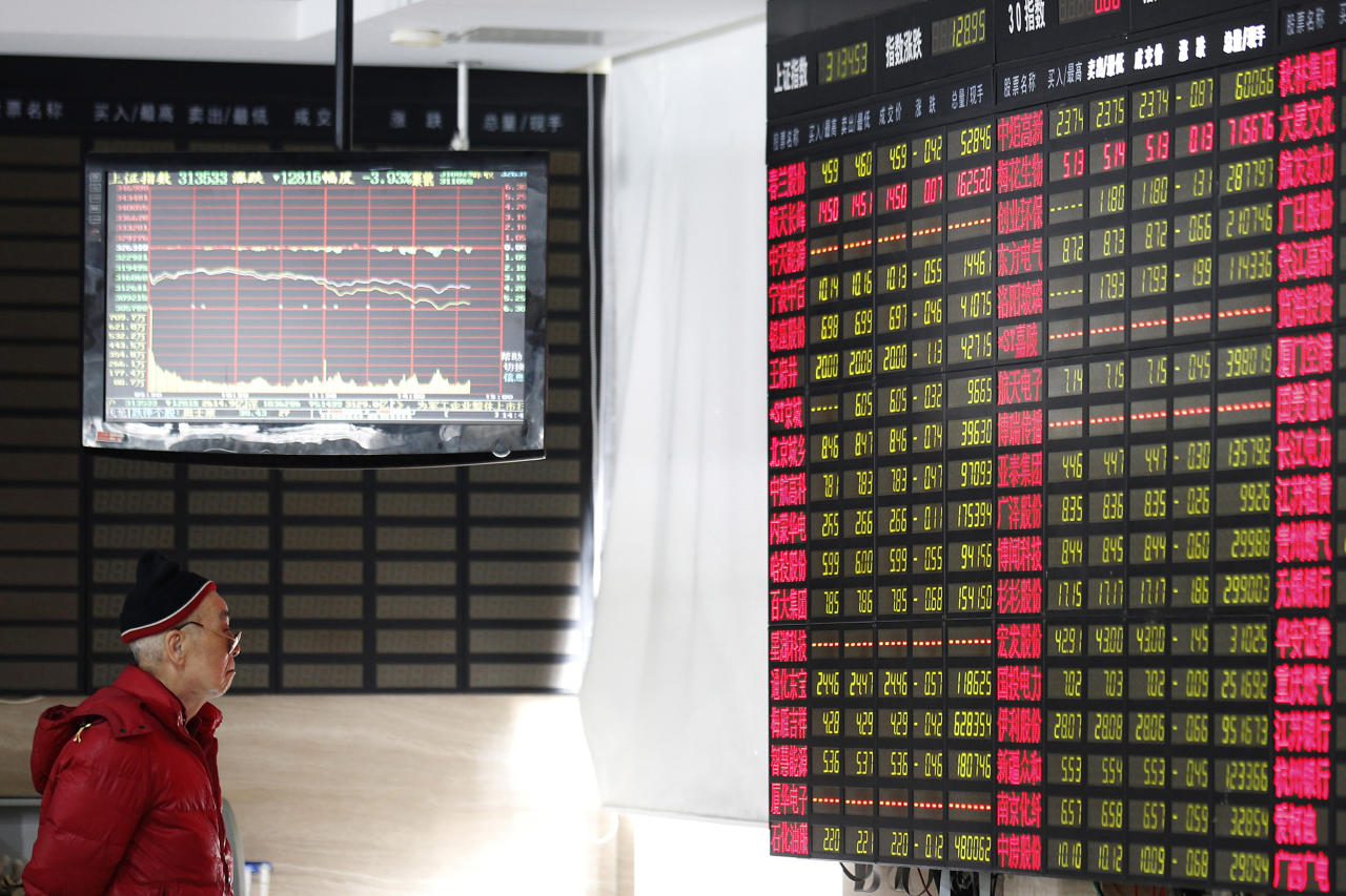 An investor looks at a stock price display screen at a brokerage house in Shanghai, Friday, March 23, 2018. Fears of a trade war roiled financial markets and sent the dollar wobbling Friday after Beijing retaliated against the Trump administration's tariff hikes by threatening import duties on U.S. goods. (AP Photo)