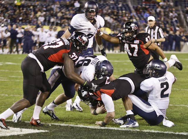 Northern Illinois quarterback Jordan Lynch breaks the goal line for a touchdown against Utah State during the first half of the Poinsettia Bowl NCAA college football game Thursday, Dec. 26, 2013, in San Diego. (AP Photo/Lenny Ignelzi)