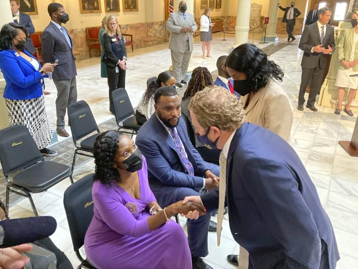 Former state Rep Bert Reeves shakes the hand of Wanda Cooper Jones, the mother of Ahmaud Arbery at the Georgia state capitol in Atlanta on Monday, May 10, 2021. Georgia Gov. Brian Kemp signed a law sponsored by Reeves repealing citizen's arrest in Georgia, partly blamed for Ahmaud Arbery's fatal shooting death near Brunswick in 2020. (AP Photo/Jeff Amy)