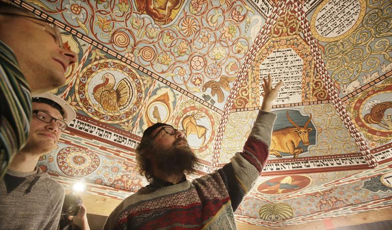 Boaz Pash,right, a rabbi based in Krakow,Poland, looks along with others at a the painted ceiling of a reconstructed wooden synagogue that dates back centuries, in Warsaw, Poland, on Tuesday March 12, 2013. The reconstructed ceiling and roof of the 17th century synagogue is a key attraction in the Museum of the History of Polish Jews, a major institution due to open next year in Warsaw.(AP Photo/Czarek Sokolowski)