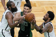 Boston Celtics forward Jayson Tatum (0) drives between Brooklyn Nets guards James Harden, left, and Kyrie Irving during the fourth quarter in Game 3 of an NBA basketball first-round playoff series Friday, May 28, 2021, in Boston. (AP Photo/Elise Amendola)