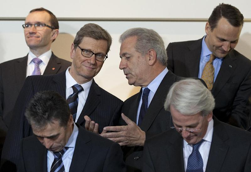 Greek Foreign Minister Dimitris Avramopoulos, center right, speaks with German Foreign Minister Guido Westerwelle, center left, during a group photo at a meeting of NATO foreign ministers at NATO headquarters in Brussels on Tuesday, Dec. 4, 2012. NATO foreign ministers are expected to approve Turkey's request for Patriot anti-missile systems to bolster its defense against possible strikes from neighboring Syria. (AP Photo/Virginia Mayo)