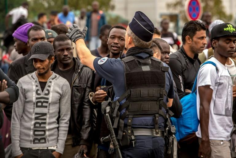 Migrants from the Calais 'Jungle' wait under police surveillance for a bus to a reception centre, set up as part of plans to dismantle the camp