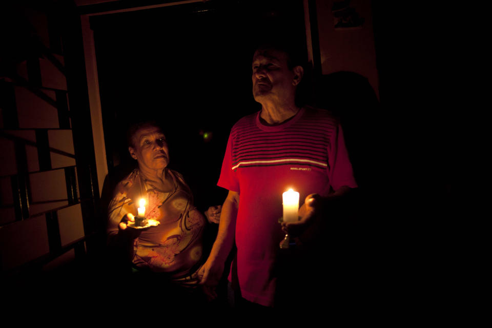 """In this April 8, 2013 photo, Pedro Martinez, 73, right, and his wife Aura, 60, hold lit candles during a power outage at their home in Valencia, Venezuela. """"This happens nearly every day,"""" Martinez says of the blackout. It's was the day's second outage. The first struck just after noon. Outside Venezuela's capital, power outages, food shortages and unfinished projects abound; important factors heading into Sunday's election to replace Venezuela's late President Hugo Chavez, who died last month after a long battle with cancer. Polls show that support for acting President Nicolas Maduro, Chavez's hand-picked successor, may be eroding and constant power outages are a testament to the neglect many Venezuelans consider inexcusable in this major oil-producing state. (AP Photo/Ramon Espinosa)"""