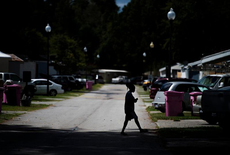 In a photo from 2018, a woman crosses the street in a mobile home park in North Carolina. (Photo: ANDREW CABALLERO-REYNOLDS via Getty Images)