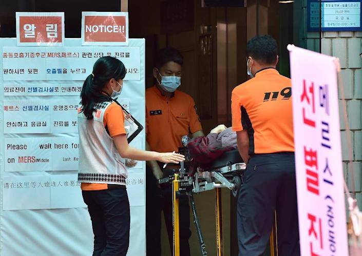 Medical emergency team carry a woman in front of a public notice on MERS, at the National Medical Center in Seoul, on June 1, 2015 (AFP Photo/Jung Yeon-Je)