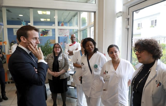 Emmanuel Macron meets staff at a care home in Paris (Ludovic Marin/AP)