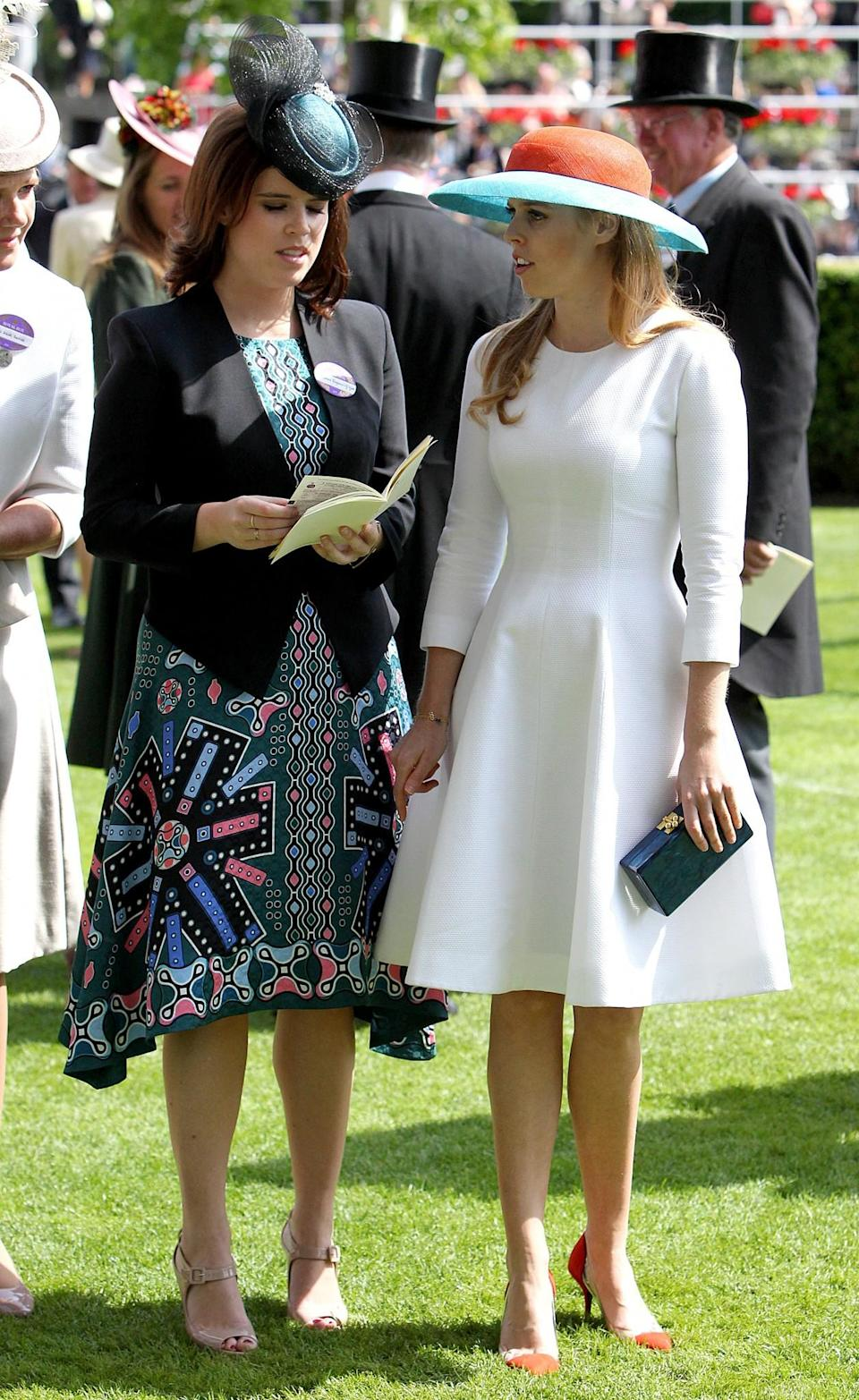 <p>The royal twosome went for completely different looks in 2015 with Eugenie going for a dark printed dress and Beatrice opting for white.<br><i>[Photo: PA]</i> </p>