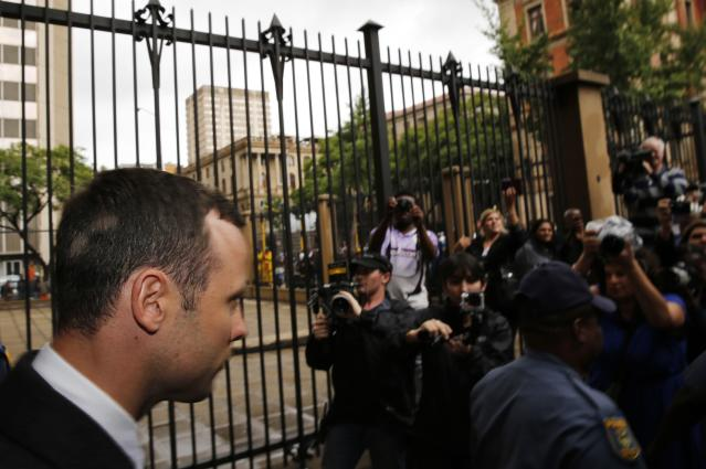 Members of the media wait to photograph Olympic and Paralympic track star Oscar Pistorius (L) as he leaves after his trial at the North Gauteng High Court in Pretoria March 4, 2014. Pistorius is on trial for murdering his girlfriend Reeva Steenkamp at his suburban Pretoria home on Valentine's Day last year. He says he mistook her for an intruder. REUTERS/Siphiwe Sibeko (SOUTH AFRICA - Tags: CRIME LAW SPORT ATHLETICS)