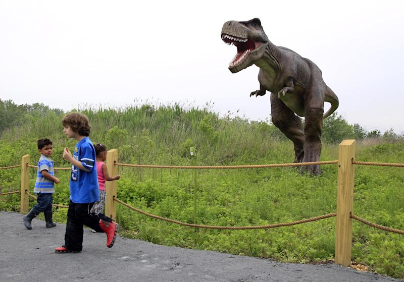 FILE - In this Friday, May 25, 2012 file photo, children stand near a life-size Tyrannosaurus Rex dinosaur model as it moves and growls in an interactive display at Field Station Dinosaurs in Secaucus, N.J. Scientists used to think T. rex stood tall, but they abandoned that idea decades ago. Now, the ferocious dinosaur is depicted in a bird-like posture, tail in the air and head pitched forward of its two massive legs. (AP Photo/Mel Evans)