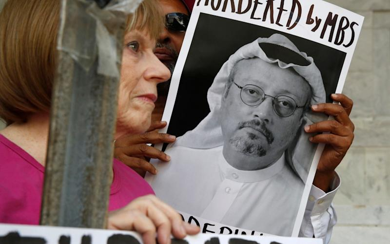 People hold signs during a protest at the Embassy of Saudi Arabia about the disappearance of Saudi journalist Jamal Khashoggi in Washington - AP