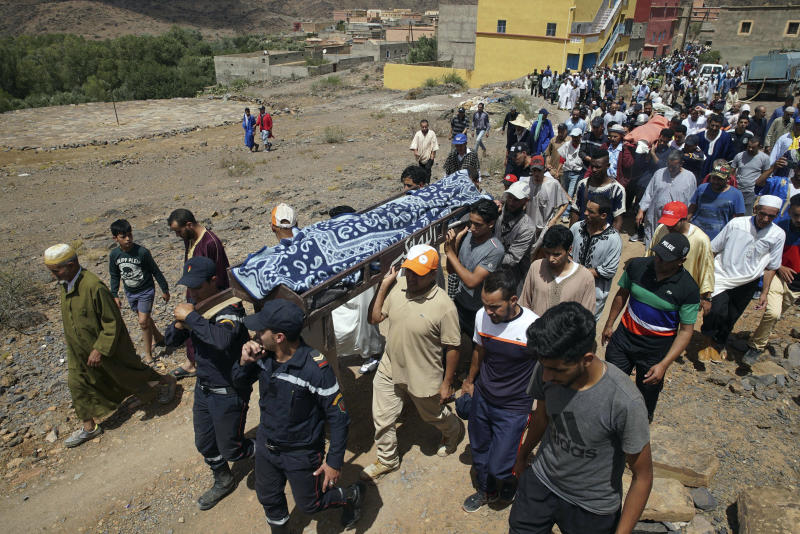 Security forces carry the body of a man who died in a flash flood in Tizert, near the southern region of Taroudant, Morocco, Thursday, Aug. 29, 2019. Morocco's official MAP news agency says that seven people watching a local soccer match in a southern village have died in a flash flood that swept across a football field on Wednesday evening. (AP Photo/Mohamed Amerkad)