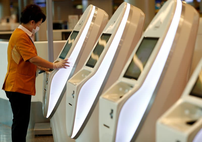 A cleaner wearing a mask in precaution of the coronavirus outbreak cleans self check-in machines at Changi Airport in Singapore