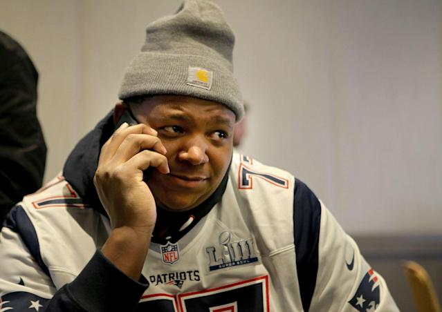Trent Brown on the phone during Super Bowl media availability, presumably not talking to the Raiders. (Getty)