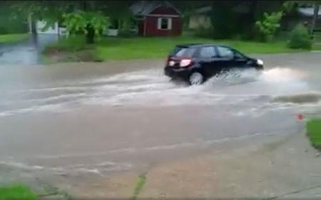 A car is seen driving through a flood, Illinois, U.S., June 18, 2018, in this still image taken from a video obtained from social media. Picture taken June 18, 2018.  Facebook/Todd Johnson/via REUTERS