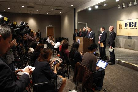 Law enforcement officials talk to reporters at a press conference regarding a shooting incident that occurred the previous day at Los Angeles airport
