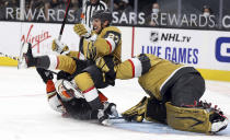 Vegas Golden Knights defenseman Shea Theodore (27) and goalie Marc-Andre Fleury (29) get taken down in a collision with Anaheim Ducks left wing Richard Rakell during the first period of an NHL hockey game Saturday, Jan. 16, 2021, in Las Vegas. (AP Photo/Isaac Brekken)