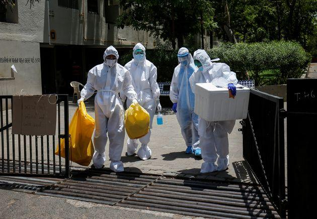 Health workers wearing protective gear leave after collecting samples during a door-to-door verification in a residential area in Ahmedabad, April 29, 2020.
