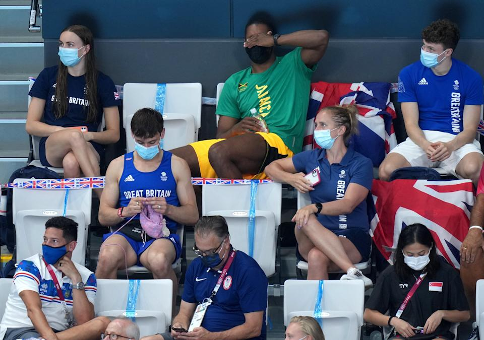 Tom Daley knits in the stands (Joe Giddens/PA) (PA Wire)