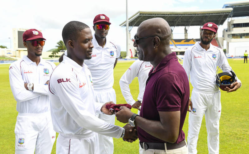 Sharmarh Brooks (L) of West Indies receives his cap on debut from Sir Vivian Richards (R) during day 1 of the 1st Test between West Indies and India at Vivian Richards Cricket Stadium in North Sound, Antigua and Barbuda, on August 22, 2019. (Photo by Randy Brooks / AFP)