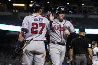 Atlanta Braves' Freddie Freeman high fives Austin Riley (27) after scoring on a double hit by Ozzie Albies during the fifth inning of a baseball game against the Arizona Diamondbacks, Monday, Sept. 20, 2021, in Phoenix. (AP Photo/Matt York)