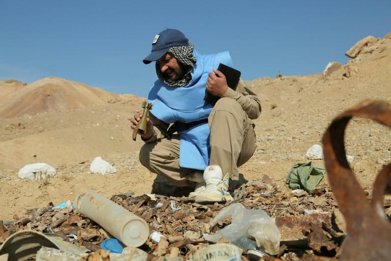 An Afghan deminer working for the Danish Demining Group holds a mortar bomb dating back to the Soviet invasion