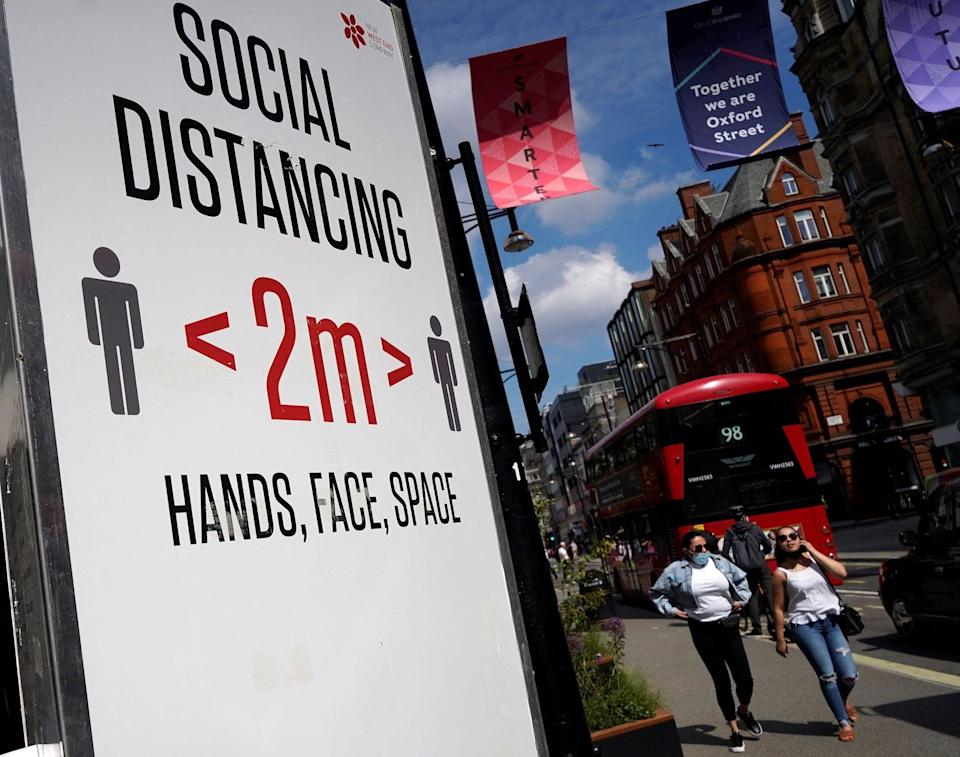 People walking past a sign on Oxford Street in London that encourages 2 meters of social distancing.