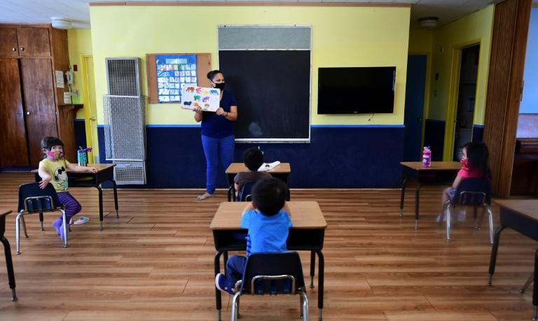 Instructor Chablis Torres (C) reads to children in a pre-school class, wearing masks and at desks spaced apart as per coronavirus guidelines during summer school sessions at Happy Day School in Monterey Park, California on July 9, 2020