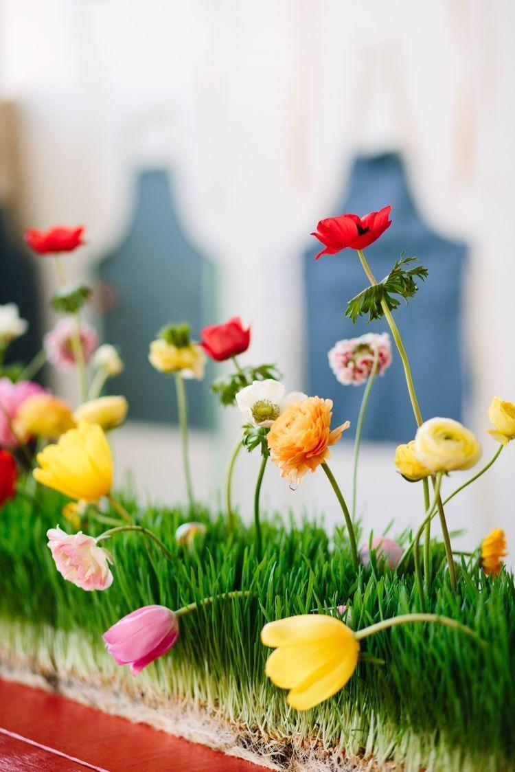 """<p>Why not make the Easter egg hunt a part of the decor? This kids' table features a fun centerpiece. To re-create, run flats of wheatgrass down the table, """"plant"""" flowers in vials of water to keep fresh, and then hide the eggs among the grass.</p><p><strong>Get the tutorial at <a href=""""http://www.twinkandsis.com/blog/hedley-bennett-x-twink-sis-easter-party?"""" rel=""""nofollow noopener"""" target=""""_blank"""" data-ylk=""""slk:Twink + Sis"""" class=""""link rapid-noclick-resp"""">Twink + Sis</a>.</strong></p>"""