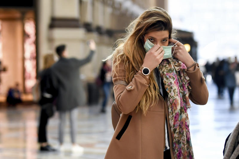 A woman wearing a sanitary mask walks through a shopping area in Milan, Italy, Monday, Feb. 24, 2020. At least 190 people in Italy's north have tested positive for the COVID-19 virus and four people have died, including an 84-year-old man who died overnight in Bergamo, the Lombardy regional government reported. (Claudio Furlan/Lapresse via AP)