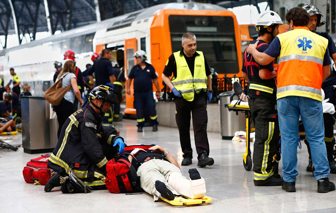 <p>An injured passenger is attended to on the platform of a train station in Barcelona, Spain, Friday, July 28, 2017. (Photo: Adrian Quiroga/AP) </p>