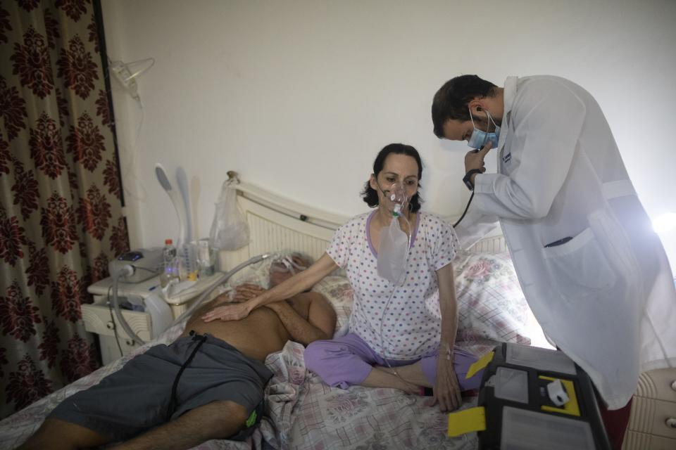 Dr. Leonardo Acosta, right, listens to the lungs of Carmen Lares who suffers from COVID-19, along with her husband, Oscar Lares, left, who is connected to a non-invasive mechanical ventilator, at their home in Caracas, Venezuela, Thursday, March 18, 2021. The Lares family has been treated at home for the last four days. (AP Photo/Ariana Cubillos)