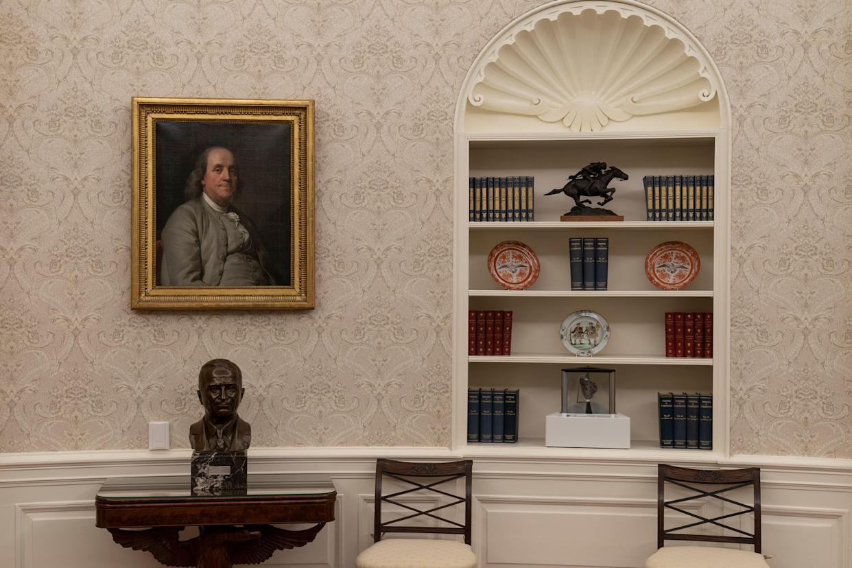 A portrait of Benjamin Franklin hangs above a bust of former President Harry Truman in President Joe Biden's Oval Office. A moon rock is displayed on the bottom shelf of a nearby bookcase. (Photo: ASSOCIATED PRESS)