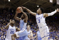 Duke's Marques Bolden (20) and Tre Jones (3) guard North Carolina's Coby White (2) during the first half of an NCAA college basketball game in Durham, N.C., Wednesday, Feb. 20, 2019. (AP Photo/Gerry Broome)