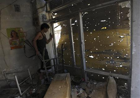 A Free Syrian Army fighter carries his weapon as he peeks out from a damaged shop in Deir al-Zor