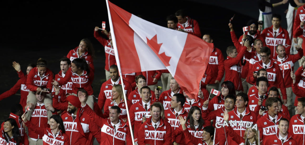 Canada's Simon Whitfield carries the flag during the Opening Ceremony at the 2012 Summer Olympics, Friday, July 27, 2012, in London. (AP Photo/Eric Gay)