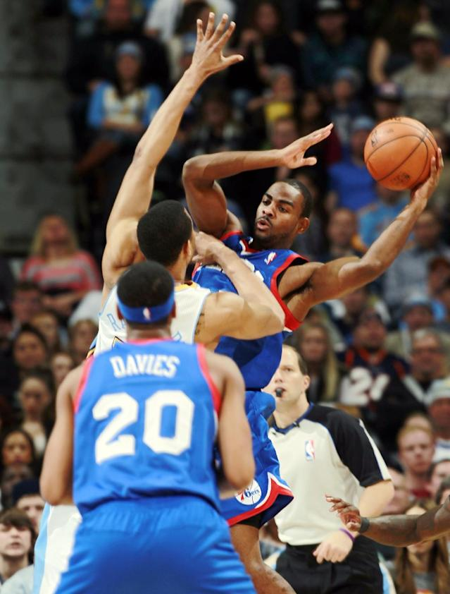 Philadelphia 76ers guard Elliot Williams, back, looks to pass to forward Brandon Davies, front, as Denver Nuggets forward Anthony Randolph covers in the fourth quarter of the Sixers' 114-102 victory in an NBA basketball game in Denver on Wednesday, Jan. 1, 2014. (AP Photo/David Zalubowski)