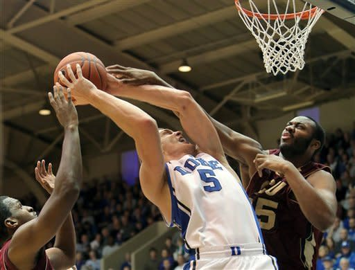 Duke's Mason Plumlee (5) is fouled on a drive by Santa Clara's Robert Garrett, right, and Raymond Cowels III, left, during the first half of an NCAA college basketball game in Durham, N.C., Saturday, Dec. 29, 2012. (AP Photo/Ted Richardson)