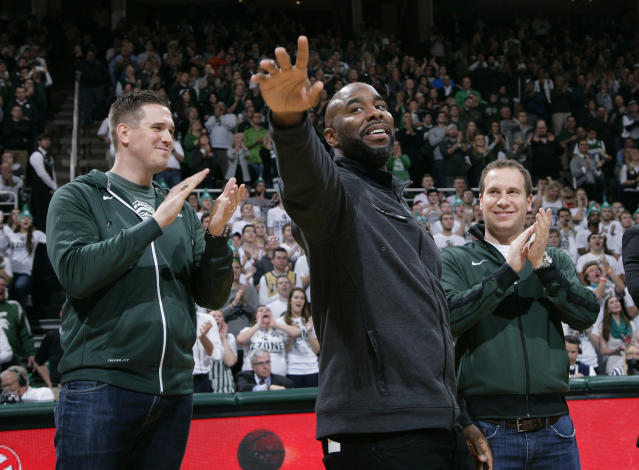 Former Michigan State player Mateen Cleaves, center, waves as he is introduced with Michigan State's 2000 national championship team during halftime of Michigan State-Florida NCAA college basketball game, Saturday, Dec. 12, 2015, in East Lansing, Mich. Also seen are Jason Andreas, left, and Mat Ishbia, right. (AP Photo/Al Goldis)